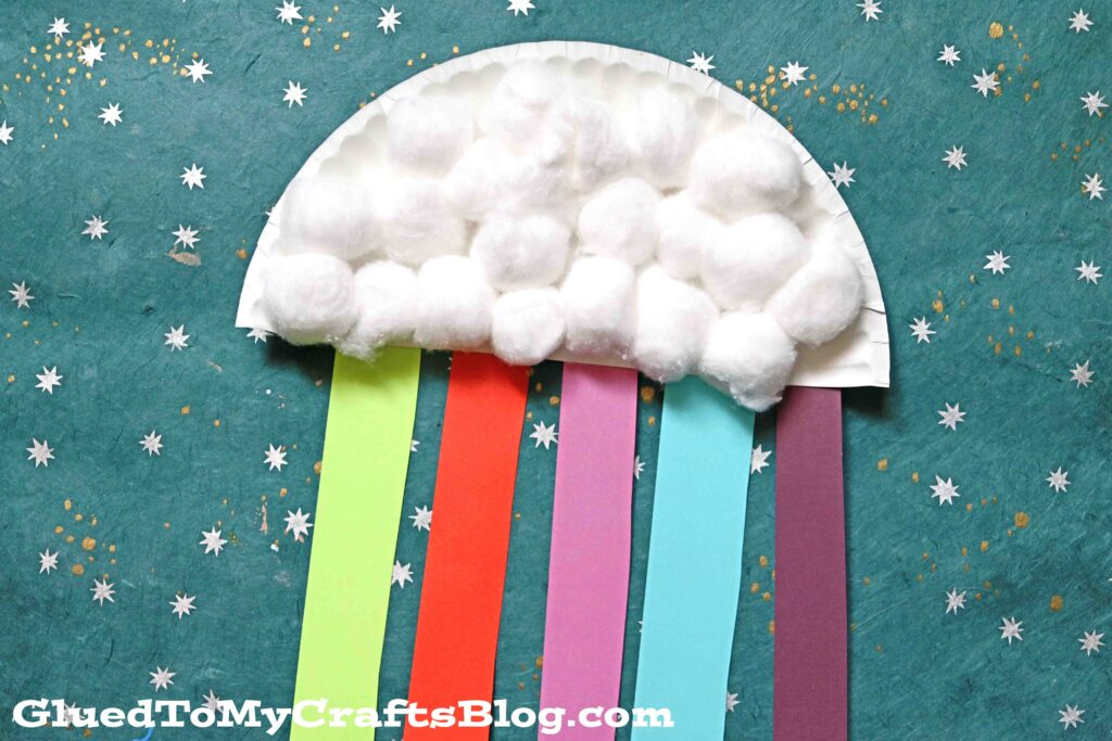 Paper plate rainbow craft with cotton ball clouds, and red, green, pink, blue, and purple streamers hanging off of it.